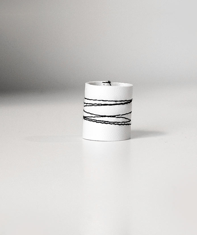 White-stitched-with-black-vegan-ring,-irregular-lines